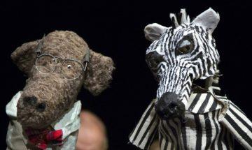 Två dockor i förgrunden, en apa och en zebra. Dockspelarna syns i bakgrunden.
