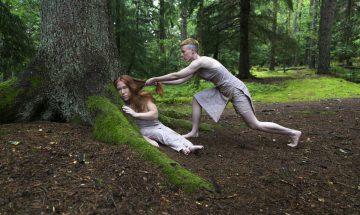Två kvinnliga dansare i skogen. Den ena drar den andre