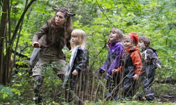 En dansare och barn i skogen